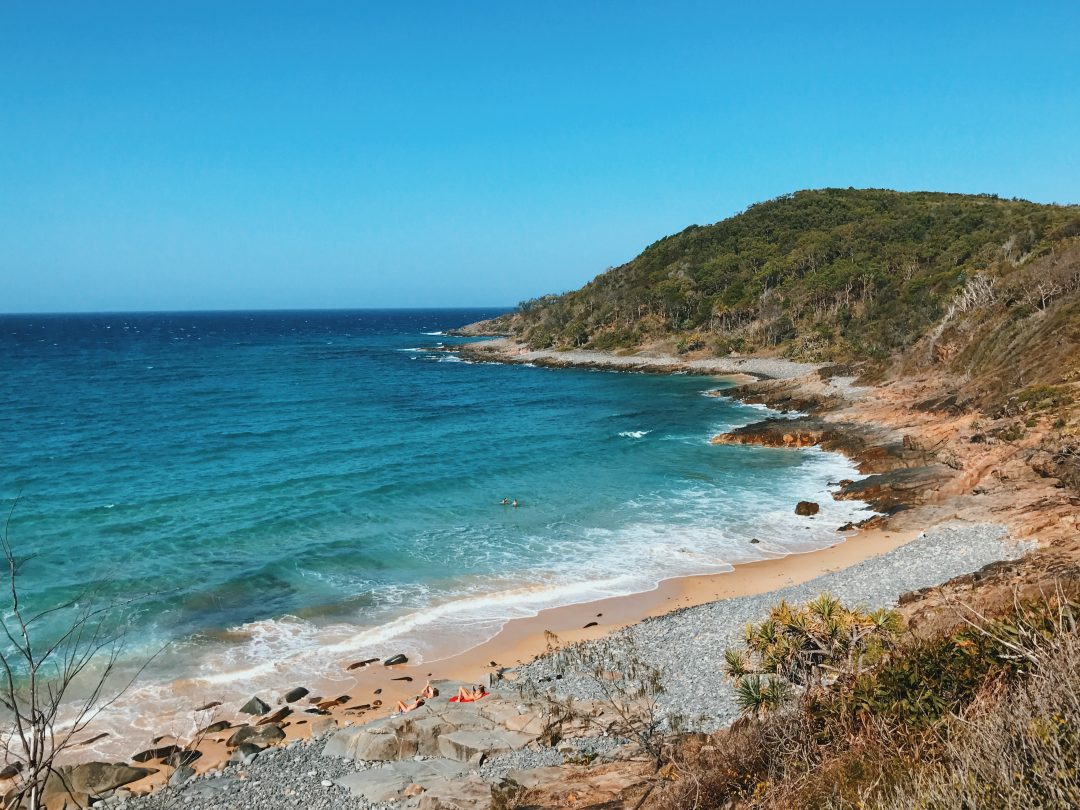 Standing at Noosa National Park, looking out towards the ocean. Rolling blue and green waves and a blue sky.