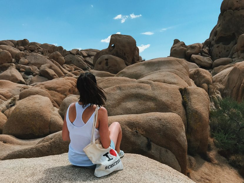 Girl sitting on a granite rock with a linen bag and sunglasses.