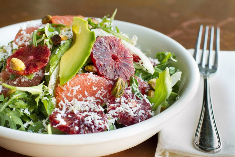 A big bowl of salad with avocado, grapefruit and nuts.
