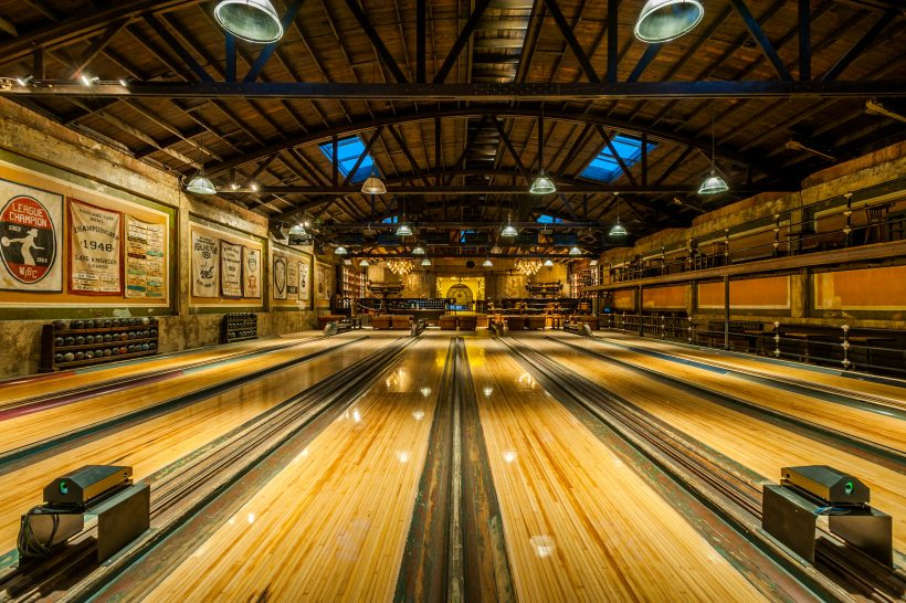 A long view of the bowling alley with a beautiful polished wooden floor.