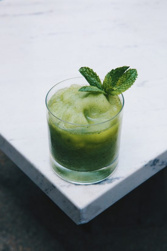 A green cocktail on a white marble desk with mint leaves.