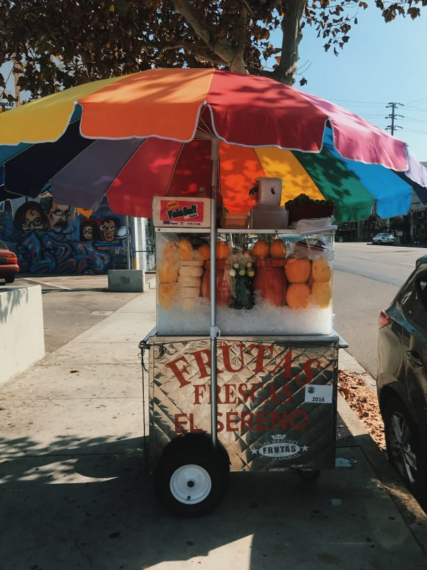 A metal food cart selling fruit with a Spanish sign.