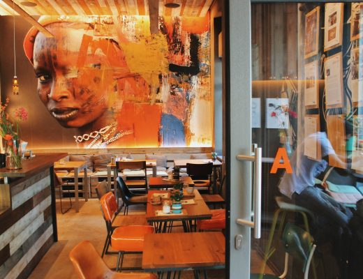 A big coffee shop with lots of chairs and tables and a big piece of artwork on the wall.