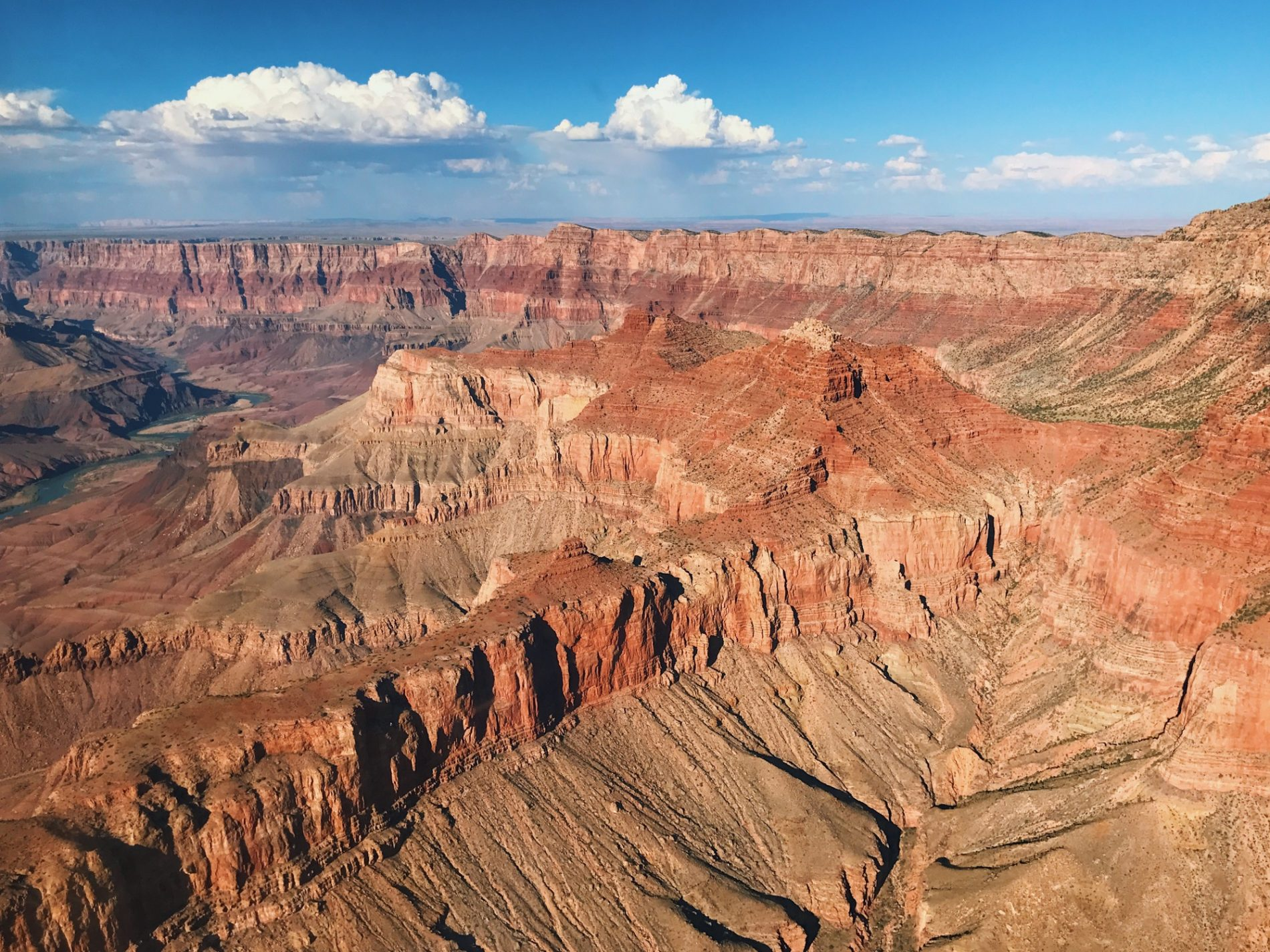 An aerial shot of the Grand Canyon from a helicopter. Strange red rock formations go as far as the eye can see.