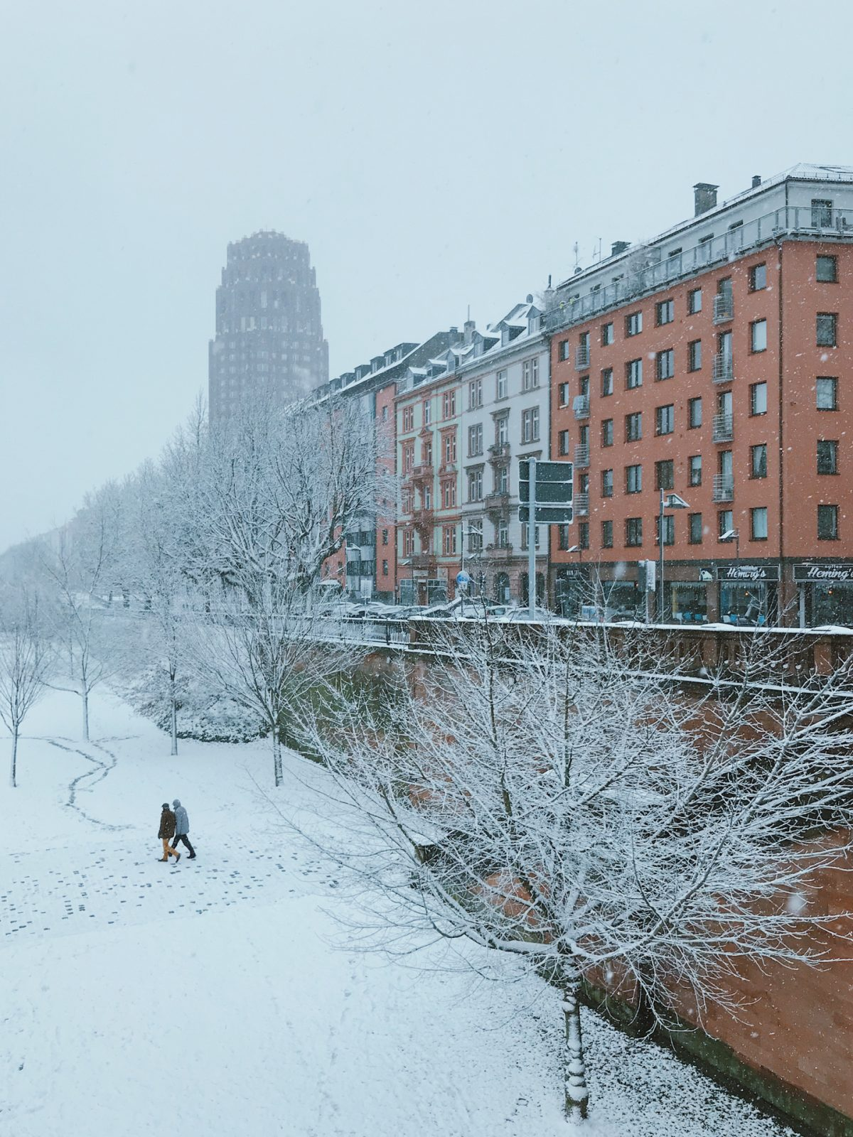 A city covered in white snow with snowflakes fallin