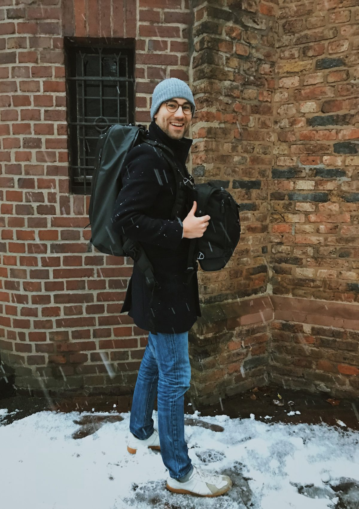 A man wearing a black hiking backpack set with snow