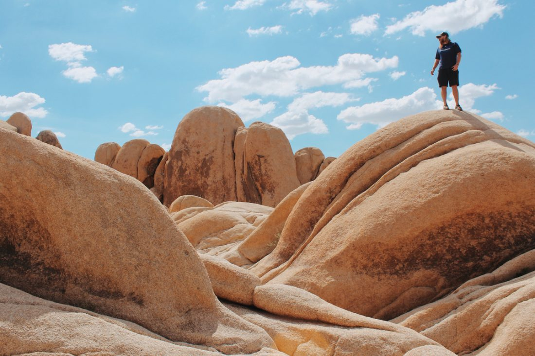 A bearded man stands on a huge boulder in the desert