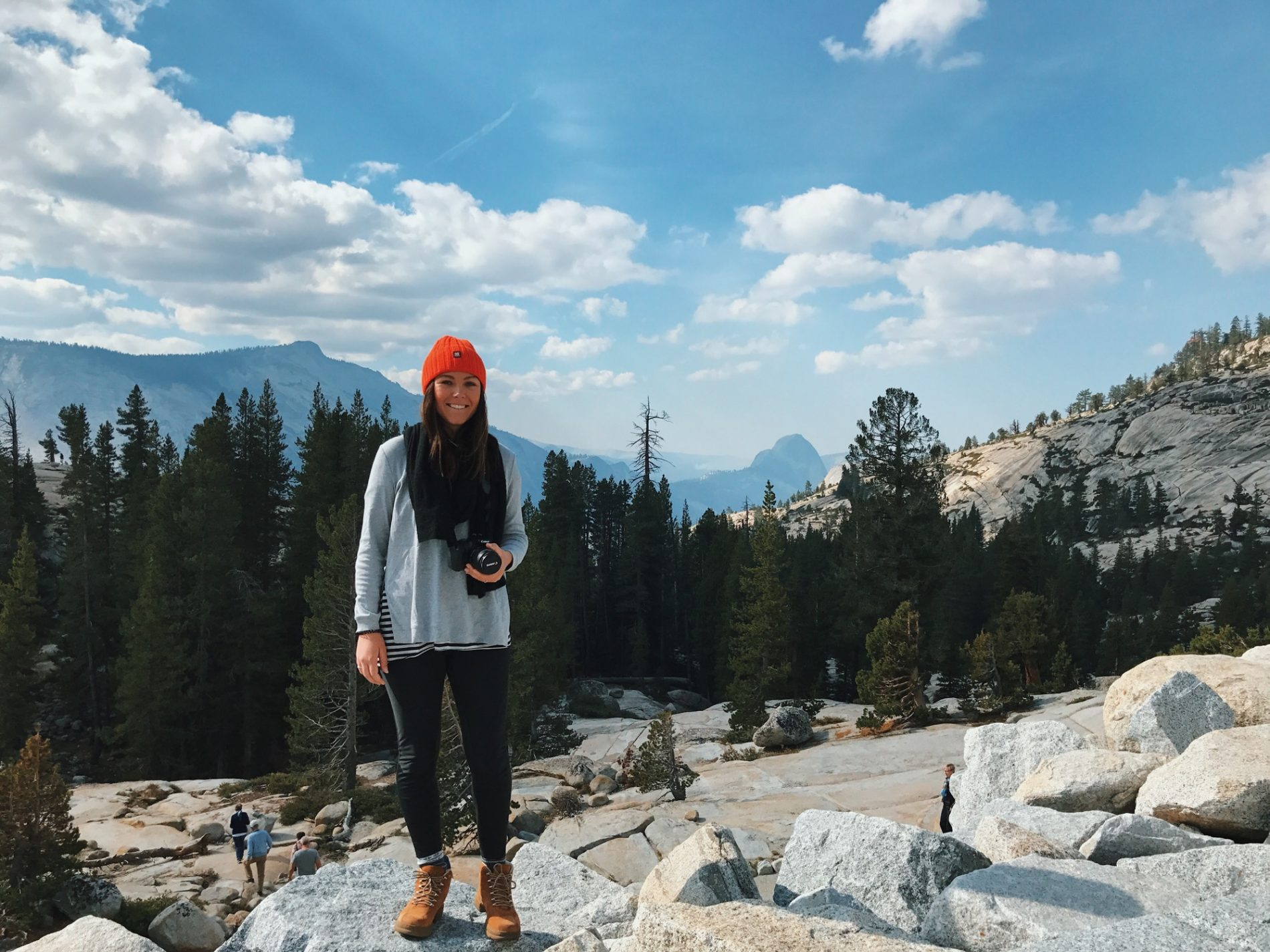 A girl stands on rock at Yosemite National Park with Half Dome in the background.