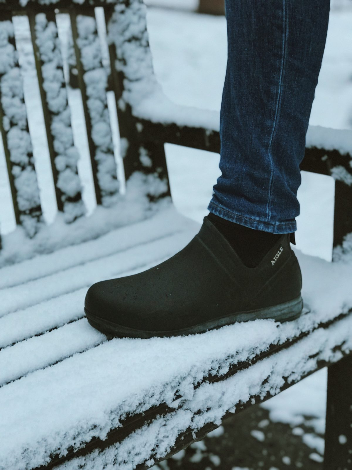 Black waterproof gumboots on a bench covered in snow