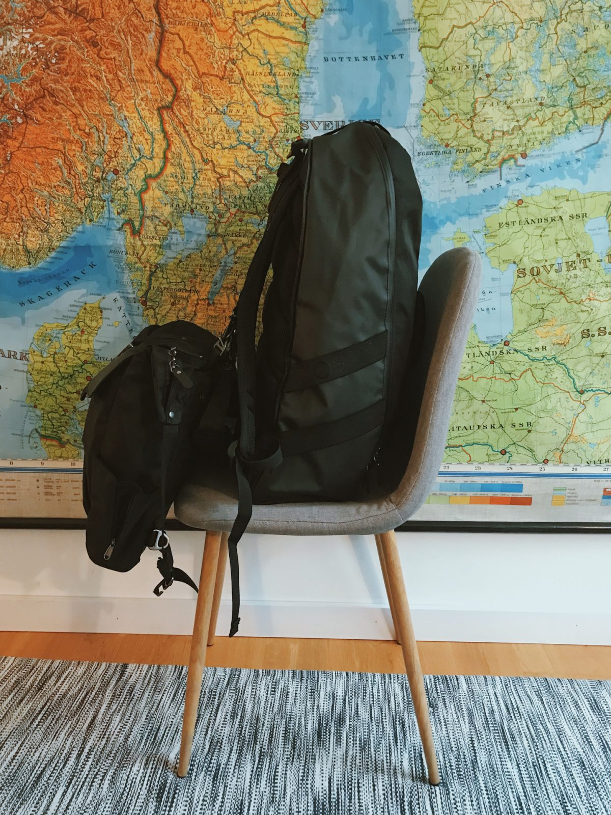 A backpacking set of bags on a grey chair in front of a map